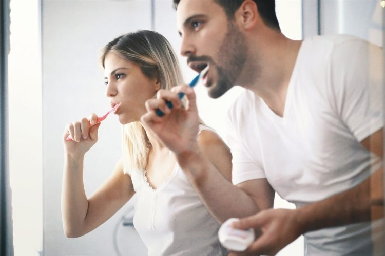Male and Female Brushing Their Teeth Together While Looking In The Mirror